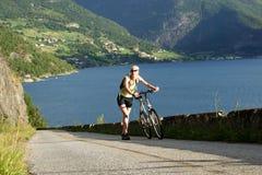 Vrouw die met fiets in de bergen loopt stock foto's