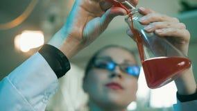 Vrouw die met flessen in een laboratorium werken stock footage