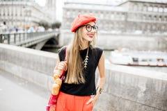 Vrouw die met Frans voedsel in Parijs lopen stock afbeelding