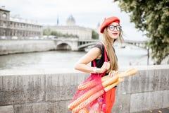 Vrouw die met Frans voedsel in Parijs lopen royalty-vrije stock afbeelding