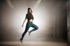 Vrouw die met gebogen been op de straat springen openluchtsport, stedelijke stijl royalty-vrije stock fotografie