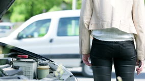 Vrouw die met gebroken auto op hulp wachten stock footage