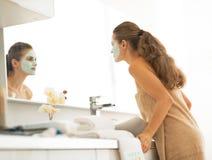 Vrouw die met gezichts kosmetisch masker in spiegel kijken royalty-vrije stock afbeeldingen