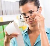 Vrouw die met glazen een ontvangstbewijs controleren Stock Foto