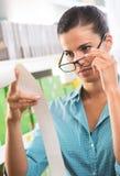 Vrouw die met glazen een ontvangstbewijs controleren Stock Foto's