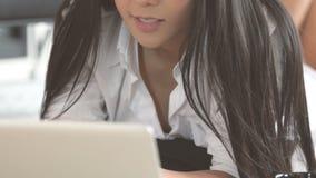 Vrouw die met haar notitieboekje die aan vloer werken liggen