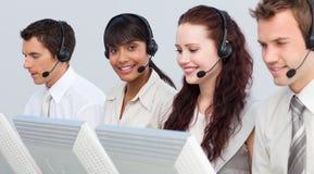 Vrouw die met haar team in een call centre werkt Stock Foto's