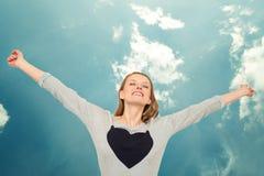 Vrouw die met hart wapens boven hoofd en hemel opheffen Royalty-vrije Stock Foto
