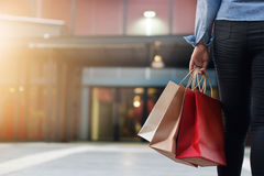 Vrouw die met het winkelen zakken op winkelcomplexachtergrond lopen