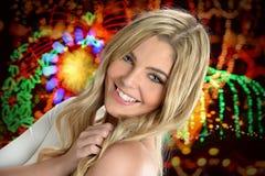 Vrouw die met Holidady-Lichten op Achtergrond glimlachen Stock Foto