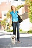 Vrouw die met hond in stadsstraat loopt Stock Foto's