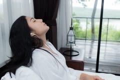 Vrouw die met hoofdtelefoons op het bed ontspannen stock afbeeldingen