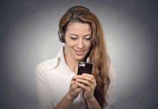 Vrouw die met hoofdtelefoons sms op smartphone het luisteren radio lezen stock foto's