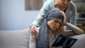 Vrouw die met kanker r?ntgenstraal, moeder ondersteunende dochter, verslechtering bekijken stock afbeeldingen