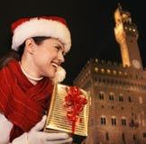 Vrouw die met Kerstmis huidige doos afstand, Florence onderzoeken Stock Afbeelding