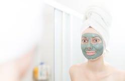 Vrouw die met klei gezichtsmasker in spiegel kijken. Royalty-vrije Stock Foto's