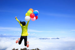 Vrouw die met kleurrijke ballons op bergpiek springen Stock Foto's