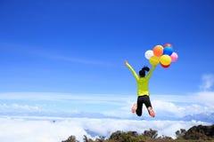 Vrouw die met kleurrijke ballons op bergpiek springen Stock Afbeelding