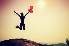Vrouw die met kleurrijke ballons op de piek van de zonsopgangberg springen Royalty-vrije Stock Foto's