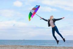 Vrouw die met kleurrijke paraplu op strand springen royalty-vrije stock afbeelding