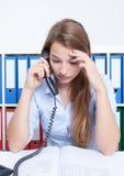 Vrouw die met lang blond haar op kantoor bij telefoon spreken Stock Foto's