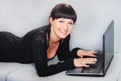 Vrouw die met laptop in huis werkt Stock Foto