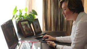 Vrouw die met laptop in huisbureau werken stock videobeelden