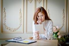 Vrouw die met laptop op droevige film op tablet letten stock foto's