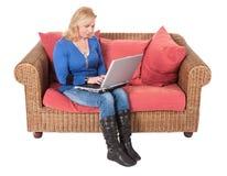 Vrouw die met laptop zitting bij een bank werkt Royalty-vrije Stock Afbeeldingen