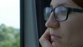 Vrouw die met Oogglazen op Treinvenster kijken stock video