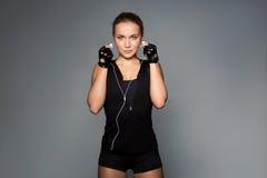 Vrouw die met oortelefoons aan muziek in gymnastiek luisteren stock foto's