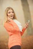 Vrouw die met oortelefoons aan muziek in park luisteren Stock Foto's