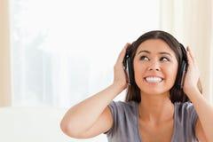 Vrouw die met oortelefoons omhoog kijkt Stock Afbeeldingen