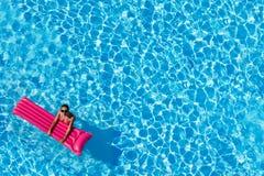 Vrouw die met opblaasbare matras in pool zwemmen stock foto's