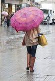 Vrouw die met paraplu onderaan straat loopt Stock Afbeelding