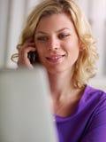 Vrouw die met PC werkt en op de telefoon spreekt royalty-vrije stock fotografie