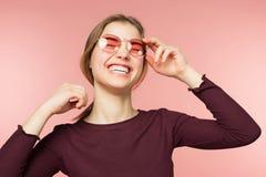 Vrouw die met perfecte glimlach en witte tanden op de roze studioachtergrond glimlachen stock foto's