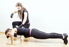Vrouw die met persoonlijke trainer uitwerken stock afbeeldingen