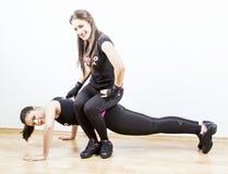 Vrouw die met persoonlijke trainer uitwerken Stock Fotografie