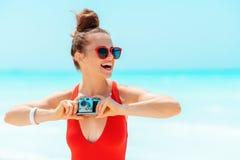 Vrouw die met retro fotocamera afstand op zeekust onderzoeken stock afbeelding
