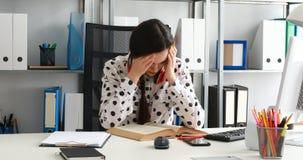 Vrouw die met rode hoofdtelefoons op schouders boek in modern bureau beduimelen stock footage
