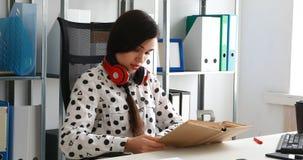 Vrouw die met rode hoofdtelefoons op schouders boek in modern bureau lezen stock video