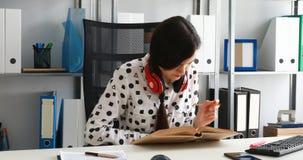 Vrouw die met rode hoofdtelefoons op schouders met potlood in notitieboekje in modern bureau schrijven stock footage