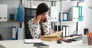 Vrouw die met rode hoofdtelefoons op schouders in potlood op papier in modern bureau schrijven stock footage