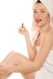 Vrouw die met rode lippenstift haar lippen likt Stock Afbeelding