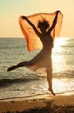 Vrouw die met rode zakdoek op strand springt stock foto