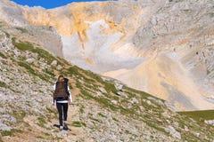 Vrouw die met Rugzak in Bergen op bovenkant wandelen stock fotografie