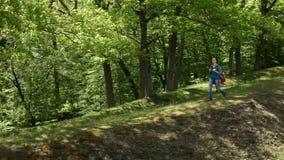 Vrouw die met rugzak op bosrand lopen stock footage