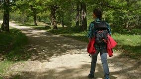 Vrouw die met rugzak op een stoffige weg in het bos lopen stock videobeelden