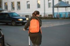 Vrouw die met schopautoped de bezige straat langs de voetgangersoversteekplaats kruisen stock fotografie